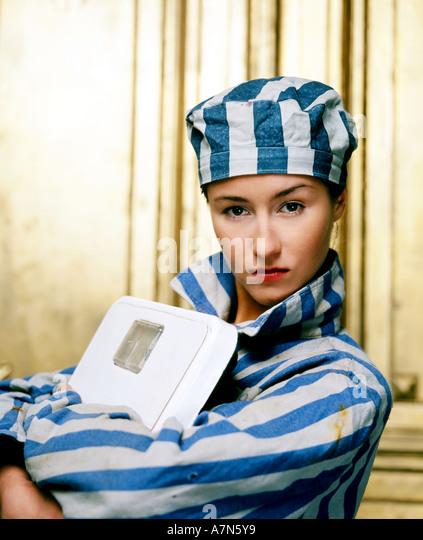 indoor studio woman young girl 20 25 dress attire jail prison shirt stripe stripes striped hat cap symbol slave - Stock Image