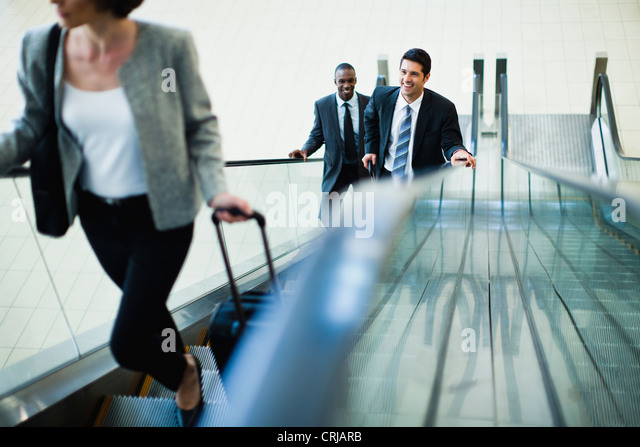 Business people riding escalator - Stock Image