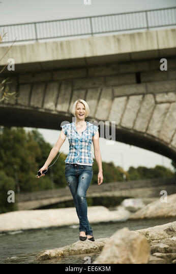 Young woman walking on the waterfront, Munich, Bavaria, Germany - Stock Image