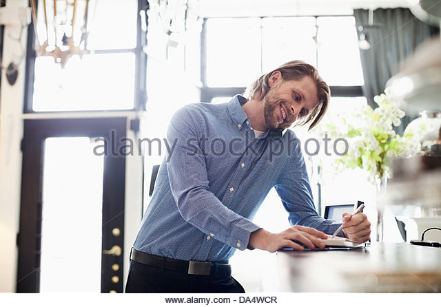 Male furniture store owner taking order by phone - Stock Image