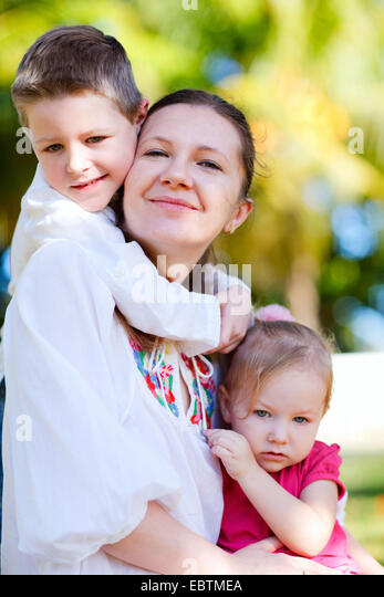 happy young mother outdoor with her little children snuggling up against her - Stock Image