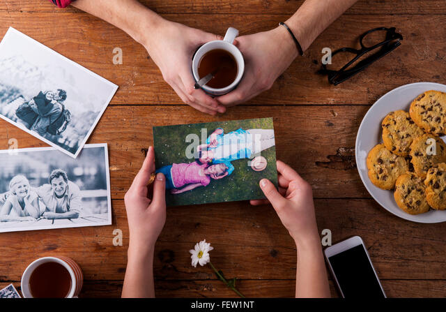 Mans and womans hands. Black-and-white photos. Couple. Tea, cookies, phone. - Stock-Bilder