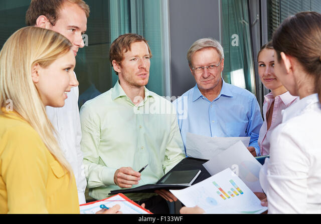 Business people having team meeting outdoors and talking to each other - Stock-Bilder