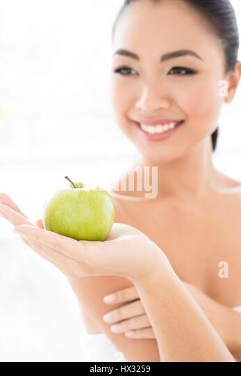 MODEL RELEASED. Young Asian woman holding apple, portrait. - Stock-Bilder
