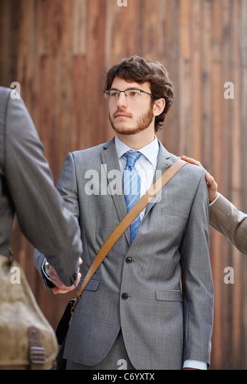 Businessmen shaking hands in courtyard - Stock Image