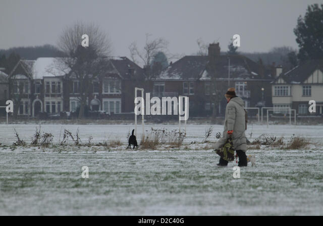 A woman walk across a field in Wanstead Flats. Despite the cold temperatures, Londoners ventured outside. Credit - Stock Image