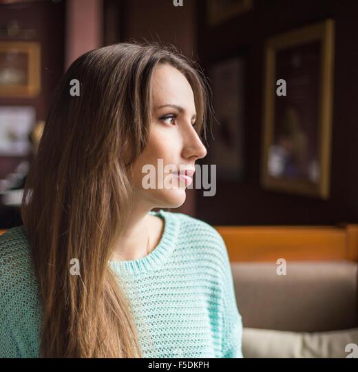 Beautiful young woman enjoying breakfast in a cafe. Pretty caucasian girl looking through window - Stock-Bilder