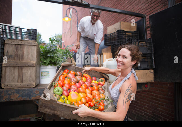 Farmers unloading crates of organic tomatoes outside grocery store - Stock Image