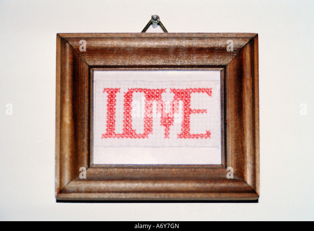 Love cross stitching in a frame and hanging on a wall - Stock Image