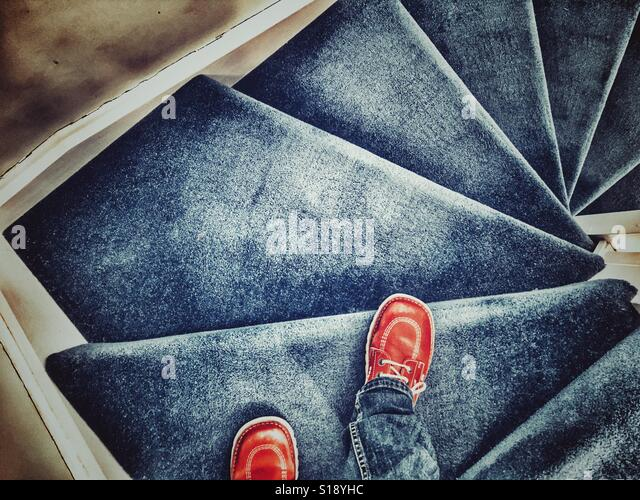 POV walking down a blue carpeted staircase - Stock-Bilder