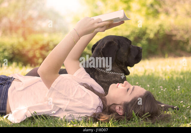 Young woman reading a book in the park with her dog - Stock Image
