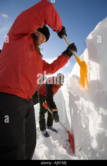 Backcountry skiers dig snow pit to check conditions - Stock Image