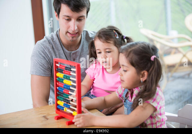 Father and daughters playing with abacus in house - Stock Image
