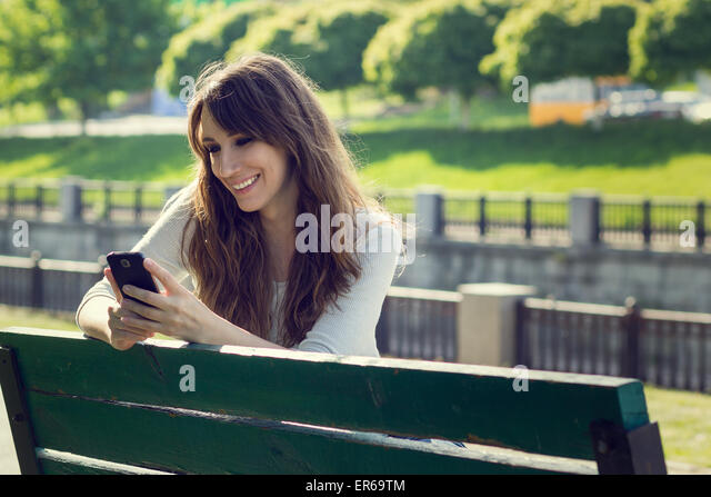 Young pretty woman chatting using phone. Smiling caucasian girl have fun with using smartphone in park - Stock Image