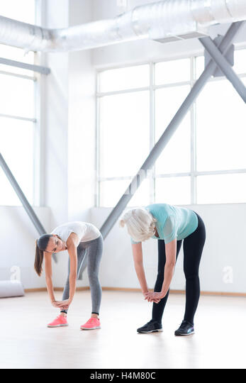 Good looking well built women trying to reach the floor - Stock Image