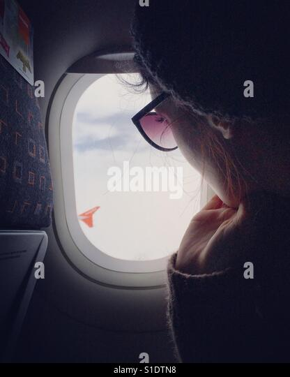 A young woman looks through a window on an airplane. - Stock Image