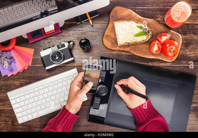 Overhead view of male hands editing photographs from smartphone on  graphic design tablet using digital pen - Stock Image