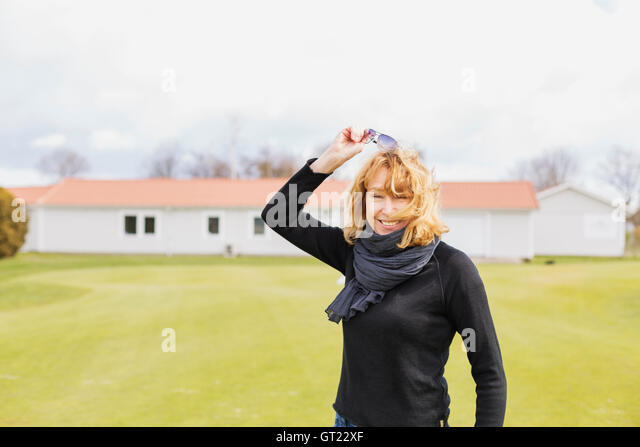 Portrait of cheerful woman removing sunglasses at golf course - Stock-Bilder
