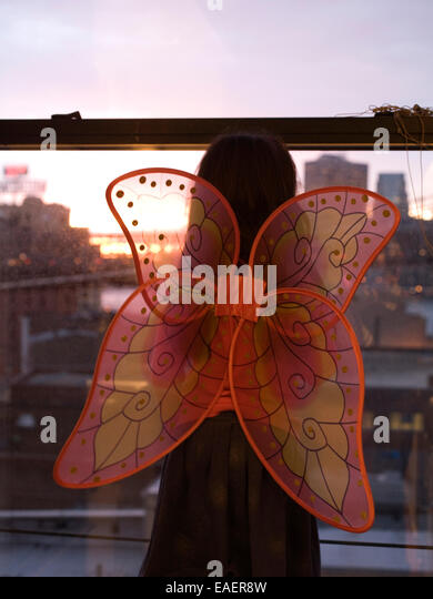 young girl with butterfly wings looking out city window at sunset - Stock Image