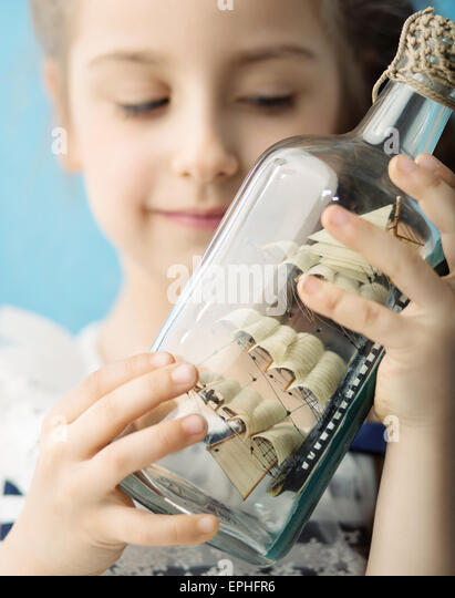 Girl holding a toy ship in the bottle - Stock Image