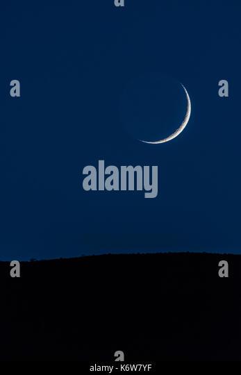 Waxing Crescent Moon Over Mountain Ridge in dark zone - Stock Image