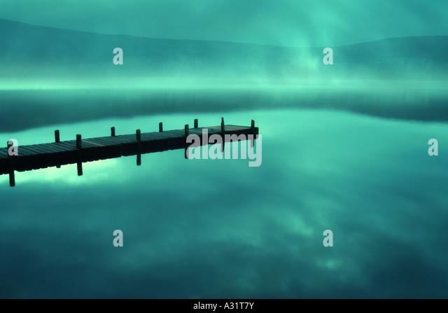 jetty on a misty lake - Stock-Bilder