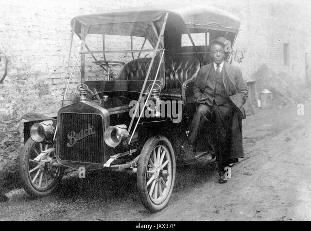 Full length shot of African American man leaning against a Buick car parked against a building, wearing a suit and - Stock Image
