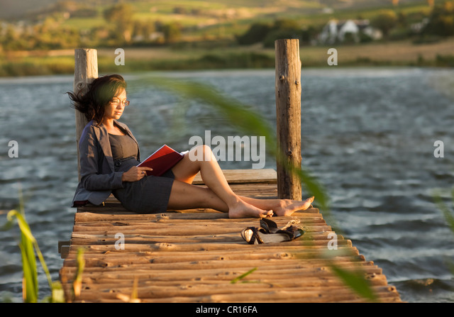 Woman reading book on dock - Stock Image