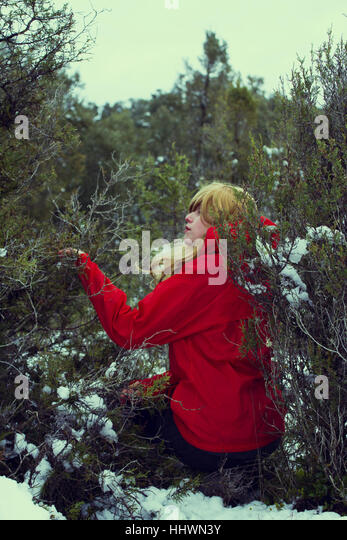Young woman with a red raincoat is lost in a forest at winter - Stock Image