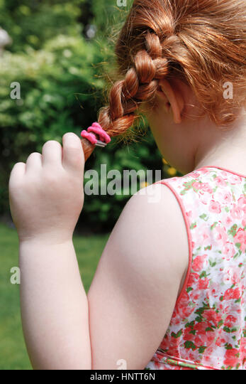 Four year old girl in her garden with plaits. View from behind. - Stock Image