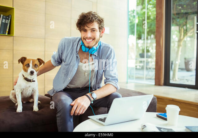 Man petting dog in office - Stock Image