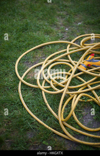 sprinkler with pipe at garden. tangled, grass, hose, water pipe. - Stock-Bilder