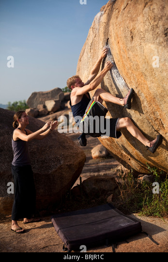 Caucasian male climber, spotted by a female, pulling onto an awkward edge in Hampi, India. - Stock-Bilder