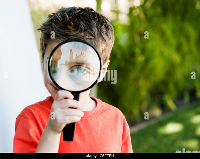 Caucasian boy looking through magnifying glass - Stock Image