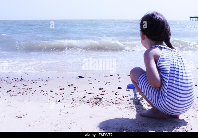 Girl crouching on beach digging in sand - Stock Image