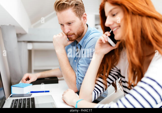 Colleagues working studying in white modern office - Stock Image