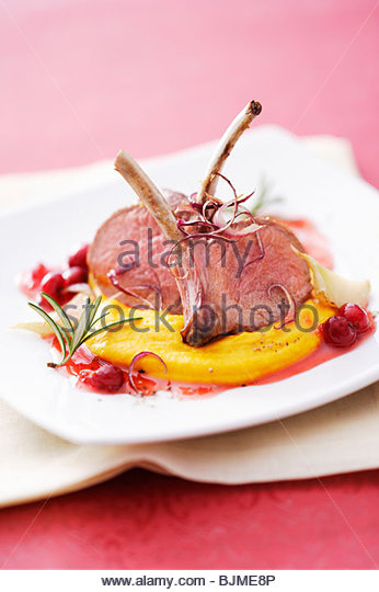 Lamb chops with pumpkin puree and cranberry sauce - Stock Image