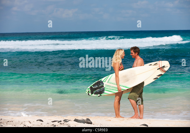 A surfing couple on beach. - Stock Image