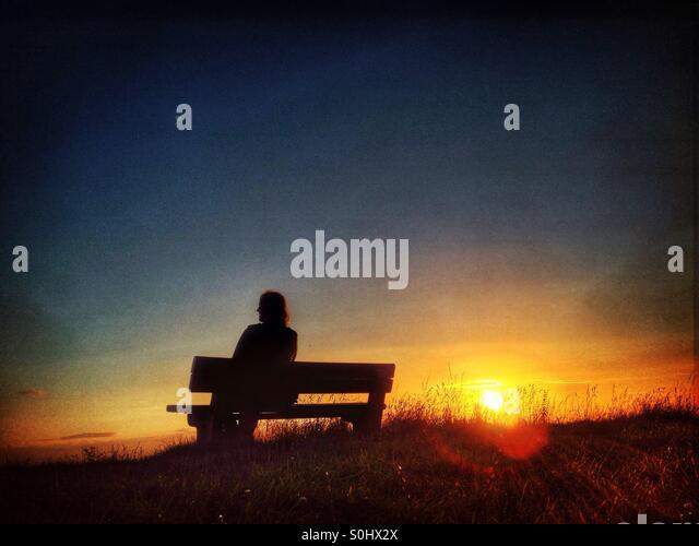 Woman sitting on bench watching the setting sun - Stock-Bilder