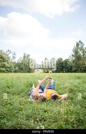 Young couple lying on grass in field, taking self portrait using smartphone - Stock Image