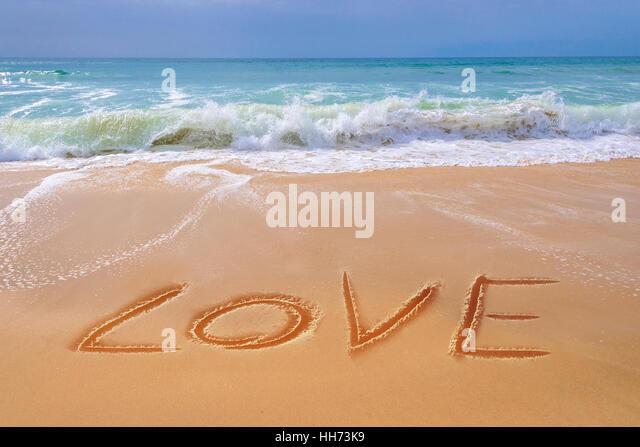 LOVE written on the sand of a beach, Saint Valentin and travel concept - Stock-Bilder