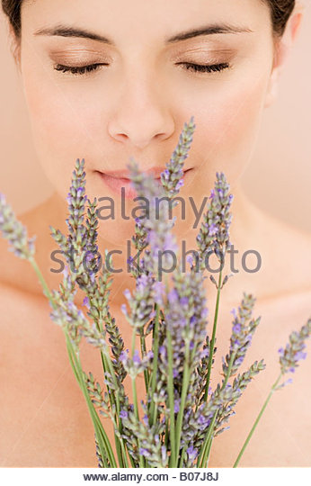 Young woman smelling lavender flowers - Stock Image