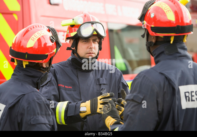 Three rescue workers talking by rescue vehicle - Stock Image