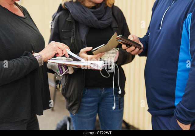 Midsection of friends holding mobile phones and diary at golf course - Stock-Bilder