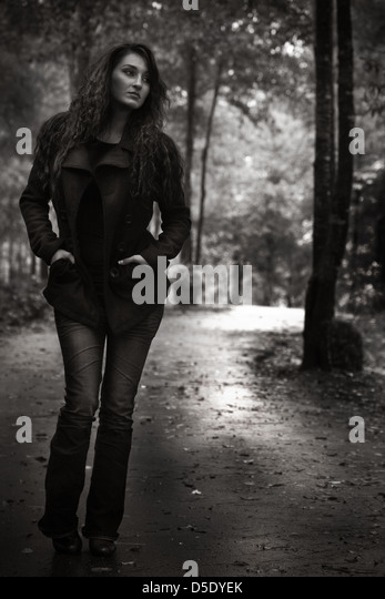 Woman walking down garden trail on rainy day - Stock Image