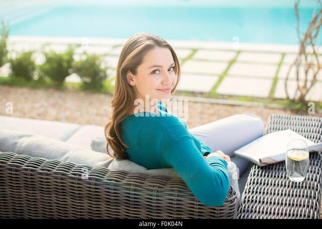 Portrait smiling woman reading magazine at luxury poolside - Stock Image