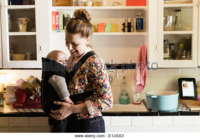 Mid adult mother with baby son in sling in kitchen - Stock Image