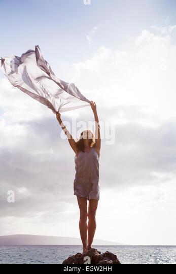 Woman standing on rock near ocean, holding fabric in the wind. - Stock-Bilder
