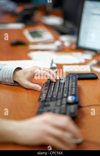 Close up of person's hands on a mouse and keyboard. - Stock Image