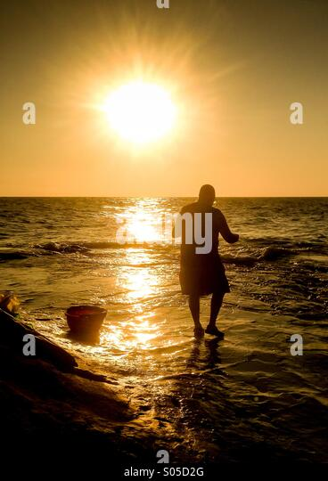 Fisherman tending float line at dawn - Stock Image